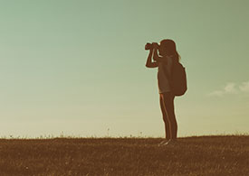 Woman with backpack looking through binoculars