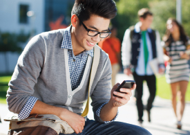 male student sitting outside looking at phone